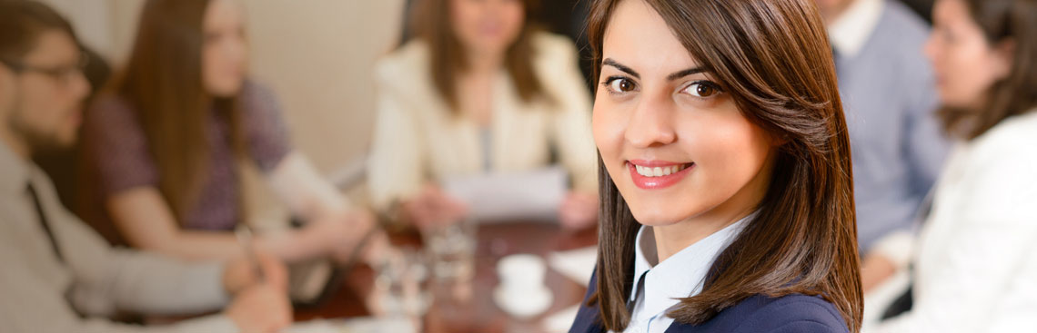 Woman smiling with meeting in the background